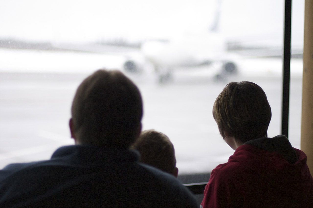 Picture of family looking out window at a plane