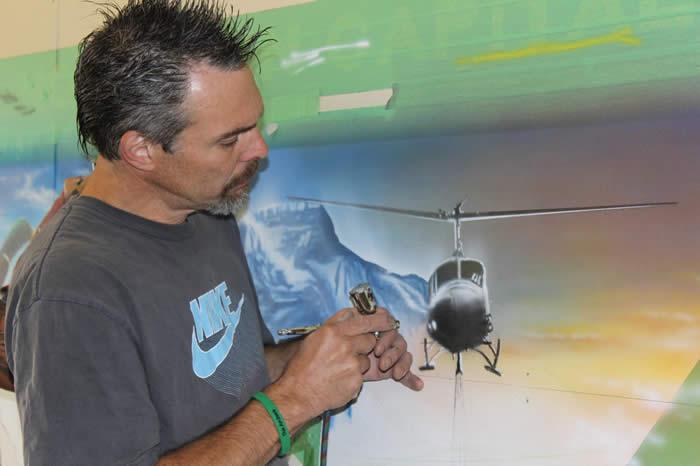 Greg Gislason airbrushing a helicopter onto mural